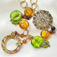 Glass bead necklace in greens browns and yellows with glass ring and filigree connector accent