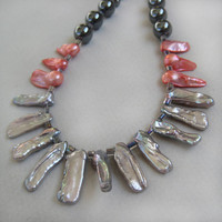 A stunning biwa pearl necklace accented with red pearl nuggets and hematite