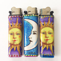 Celestial Lighters with Glittering Sun and Moon Artwork. **Sold Separately**