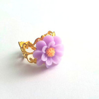 Lila Colored resin cabochon daisy ring atop gold plated adjustable metal filigree