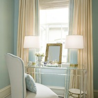 bedrooms - Acrylic lucite desk ivory window treatments blue lamps cornice box blue walls Kelley Interior Design via House of Turquoise. Love