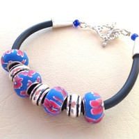 Polymer clay floral bead bracelet in blue and fuchsia on rubber cord