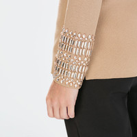 Side-slit sweater with jewelled cuffs