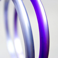 A pair of moon glow lucite bangles. Purple and silver grey from the 1960s,