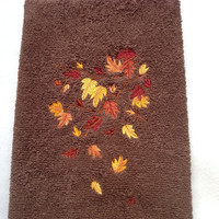 Fall leaves in colors yellow orange gold burnt orange embroidered on a brown towel.
