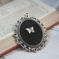 Cameo pendant with filigree frame, black felt and silver butterfly design
