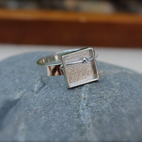 sterling silver shadow box ring. wire with silver bead that moves. box ring. square top textured background. Modern. Minimalist