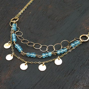 Multi strand layered gold filled necklace with blue topaz and gold filled discs. Handmade, modern triple strand gold necklace.