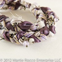 Purple and grey braided fabric wrap bracelet with dangle beads.