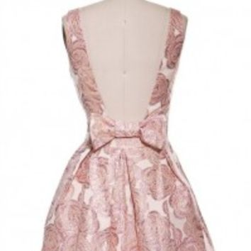 Go all out with this trendy statement flare dress featuring pink colored rose with metallic gold outline print all over. Sexy deep V-neckline front with plunging open back with bow detailing, side zipper closure, sleeveless. Fully lined. This flirty dress