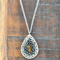 Layers of You Pendant - $58.00: From ourchoix.com, a double chain of silver gives way to a oval shaped pendant with green, purple, and gold.