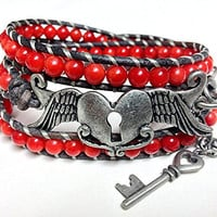 Red beaded leather wrap bracelet with a winged heart lock and key and red coral