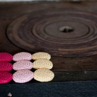 Crocheted cotton and wood trivet, hot pad in pastels. Crocheted circles in pink, hot pink and yellow.