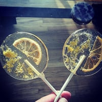 Lavender flavored lollipops with lemon slices and dried lavender flowers