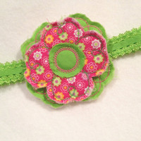 Frayed shabby flower in pinks and greens and is attached to a bright green headband.