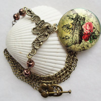 Round locket with crown and roses on front cover adorned with copper color beads and bronze accents
