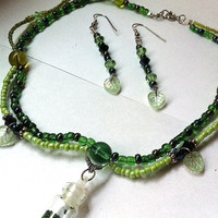 scalloped green beaded choker with crystals, leaves, and mini glass bottle