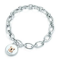 Tiffany & Co. -  Tiffany Locks vintage round charm in silver and 18k rose gold on a bracelet.