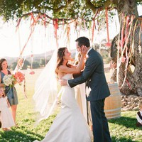 Outdoor wedding ceremony; pink streamers hung from tree
