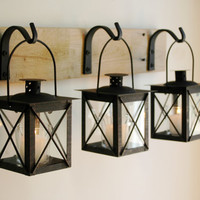 Black Lantern Trio hanging from wrought iron hooks on recycled wood board for unique wall decor, home decor, bedroom decor