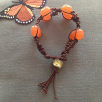 Handmade brown macrame cord with peach colored beads with glass swirl bead closure.