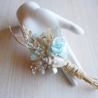 Seashore Boutonniere, made of dried grass, seashells, light teal rose, light teal babies breath and twine.