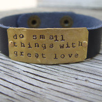 A riveted, 1/2 inch wide leather cuff bracelet with hand stamped brass distressed and embellished wording of your choice